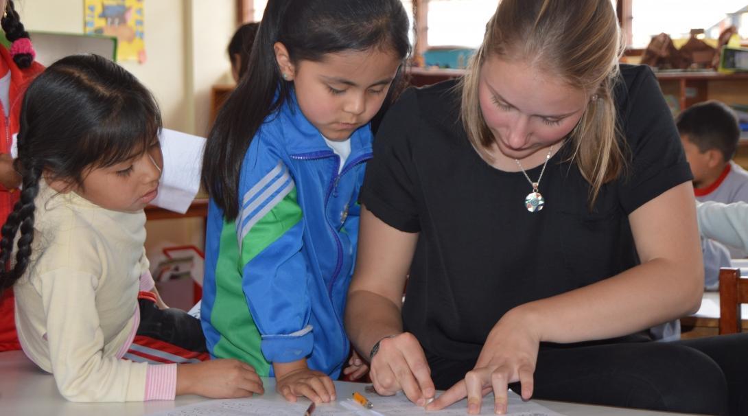 Voluntaria de enseñanza en Perú explica a sus estudiantes un ejercicio.